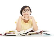 Ung studentflicka som tänker med boken över vit bakgrund Fotografering för Bildbyråer