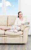 Ung studentkvinna med minnestavlan på soffan fotografering för bildbyråer