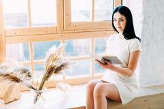 Ung studentkvinna som sitter i gruppl?sningen en bok arkivfoto