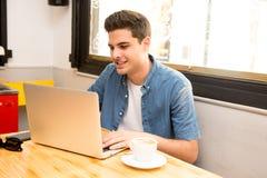Ung studentman som arbetar och studerar på datoren i coffee shop fotografering för bildbyråer