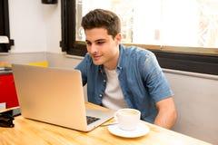 Ung studentman som arbetar och studerar på datoren i coffee shop arkivfoto
