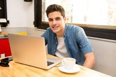 Ung studentman som arbetar och studerar på datoren i coffee shop arkivfoton
