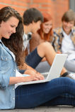 Ung studerande kvinna som använder bärbara datorn utanför högskolan Arkivfoton