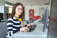 Ung studie för kvinnlig student i skolaarkivet, henne som använder bärbara datorn och direktanslutet lär, tillbaka till skolutbil fotografering för bildbyråer