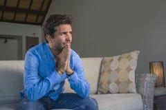 Ung sufferi för tröttad och deprimerad hemmastadd soffasoffakänsla för attraktivt och stiligt ledset latinskt mansammanträde förk royaltyfri bild
