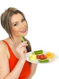 Ung sund attraktiv kvinna som äter fem en dagfrukt och grönsaker Arkivbild