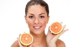 Ung sund flicka som rymmer en apelsin i hans hand Royaltyfria Bilder
