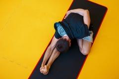Ung sund grabb som gör övningar i idrottshallen royaltyfri foto