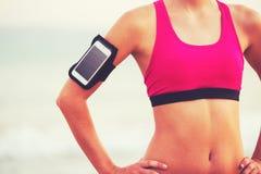 Ung sund konditionkvinna med den smarta telefonen arkivbild