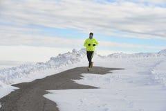 Ung sund sportmanspring i snöberg i hård genomkörare för slingalöpare i vinter arkivfoton