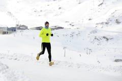 Ung sund sportmanspring i snöberg i hård genomkörare för slingalöpare i vinter royaltyfri foto