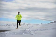 Ung sund sportmanspring i snöberg i hård genomkörare för slingalöpare i vinter arkivfoto