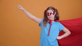 Ung superhero som rymmer hennes näve hög in mot himlen arkivfilmer
