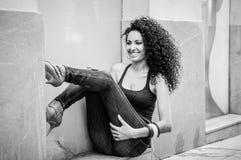 Ung svart kvinna, afro frisyr, i stads- bakgrund arkivfoton