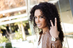 Ung svart kvinna, afro frisyr, i stads- bakgrund royaltyfri fotografi