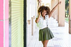 Ung svart kvinna, afro frisyr, i stads- gata med headphon fotografering för bildbyråer