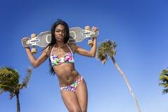 Ung svart kvinna i bikinin som rymmer en skateboard bak hennes huvud royaltyfria foton