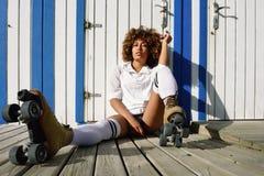 Ung svart kvinna på rullskridskor som sitter nära en strandkoja Arkivbild