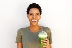 Ung svart kvinna som ler med den nya koppen av fruktfruktsaft Arkivbilder