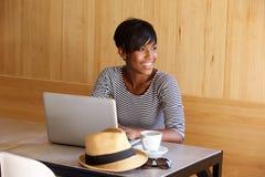 Ung svart kvinna som ler och använder bärbara datorn Arkivbild