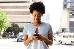 Ung svart kvinna som lyssnar till musik på hennes mobiltelefon arkivbild