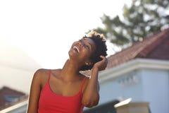 Ung svart kvinna som utomhus skrattar med hennes hand i hår arkivfoto
