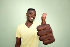 Ung svart man som gör en gest tummar upp tecken vid den gröna väggen Arkivfoto