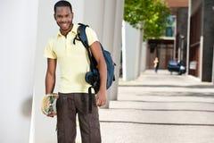 Ung svart manlig med skateboarden och påsen Royaltyfria Bilder