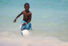 Ung svart pojke som spelar fotboll på stranden royaltyfri fotografi