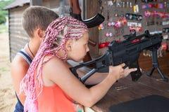 Ung syskongrupp som siktar med det pneumatiska geväret i en skjuta galery, sidosikt arkivbilder