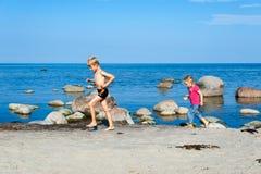 Ung syskongruppspring på stranden Arkivbild