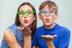 Ung syster och broder med fräknar på deras framsidor som tillsammans poserar över ljus - blå bakgrund, ser och överför kyssen Royaltyfria Bilder