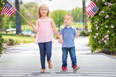 Ung syster och broder Waving American Flags på parkera Royaltyfri Fotografi