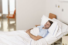 Ung tålmodig man som ligger på sjukhussäng som vilar tröttat se ledset och deprimerat bekymrat royaltyfri foto