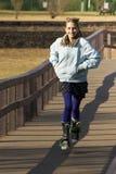 Ung Teen Crossingbro på Strollerskridskor royaltyfri foto