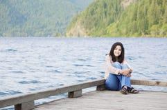Ung teen flicka som tyst kopplar av på lakepir, Arkivfoto