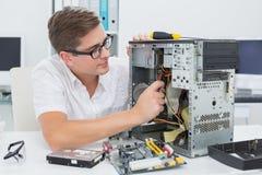 Ung tekniker som arbetar på den brutna datoren arkivfoton