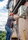 Ung tekniker som reparerar den betingande enheten för utvändig luft Royaltyfria Bilder