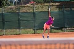 Ung tennisspelare som tjänar som bollen med hög inverkan arkivfoto