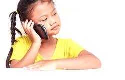 Ung thailändsk flicka som använder smartphonen som isoleras på vit Arkivfoto