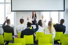 Ung tillfällig asiatisk affärskvinnaledare som gör en presentation och frågar för åsikt i mötet affären chairs konferensskrivbord arkivbild