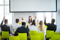 Ung tillfällig asiatisk affärskvinnaledare som gör en presentation och frågar för åsikt i mötet affären chairs konferensskrivbord arkivbilder