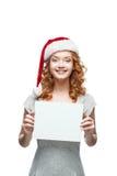 Ung tillfällig flicka i tecken för santa hattholding Arkivbild