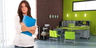 Ung tillfällig kvinna i ett kontor arkivbild