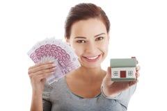 Ung tillfällig kvinna med pengar och huset. Royaltyfri Foto