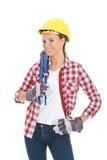 Ung tillfällig kvinna med plubmerskiftnyckeln och säkerhetshjälmen. royaltyfri fotografi