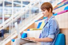 Ung tillfällig kvinna som arbetar på bärbara datorn i ljus öppen inre Arkivfoton