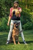 Ung tillfällig kvinnalek med hunden i trädgård Royaltyfria Bilder