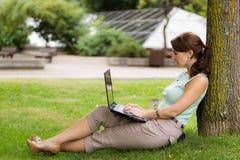 Ung tillfällig kvinnastudent i parkera som arbetar på bärbara datorn Arkivfoton