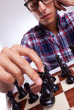 Ung tillfällig man som flyttar hans schackstycke Arkivfoton